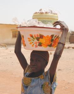 Ein Mädchen verkauft im Dogon Land Erdnüsse.